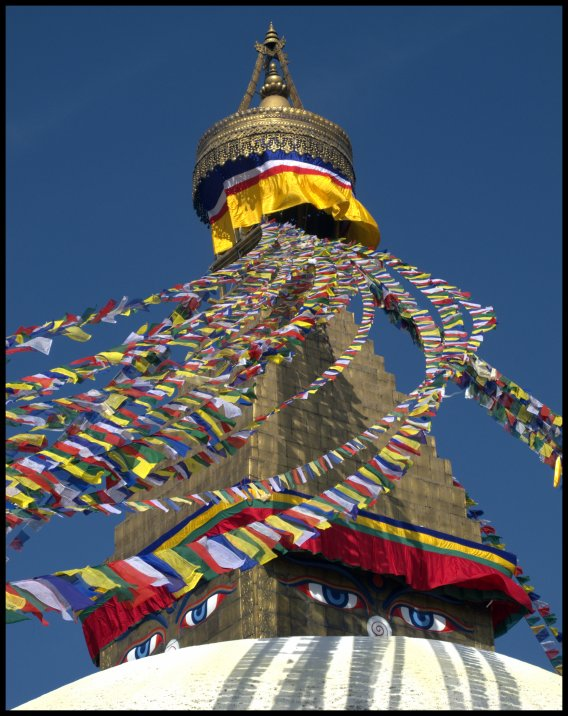 Prayer flags adding colour around Buddha's eyes on the stupa